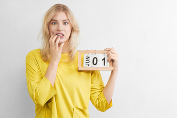 Puzzled attractive woman in yellow clothes with calendar thinks about preparing for vacation trip, not much time left until first day of summer