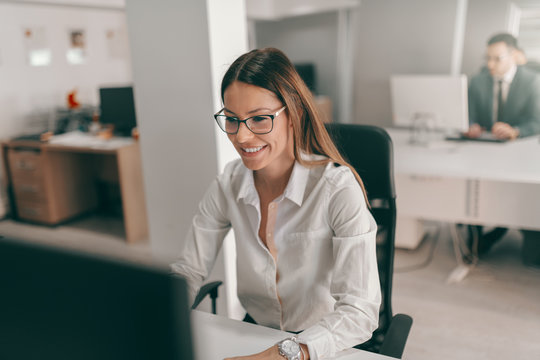Young Caucasian secretary in shirt and with eyeglasses using computer for work. In background employee working. I'm in corporate business. What is your superpower?