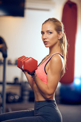 Woman lifting dumbbells and looking at camera. Side view. Healthy lifestyle concept.