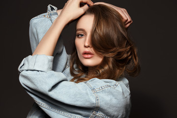 Beautiful brunette girl with long flowing hair dressed in jeans jacket poses holding her hands on her head on the dark background in the studio