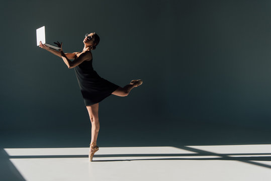 young ballerina in black dress and eyeglasses dancing with laptop