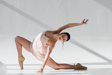 young ballerina in pointe shoes and pink dress dancing
