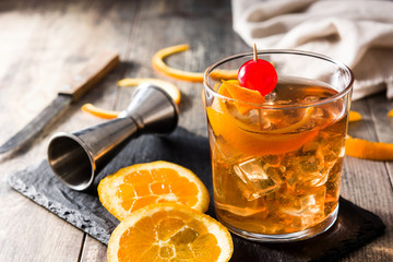 Old fashioned cocktail with orange and cherry on wooden table Wall mural