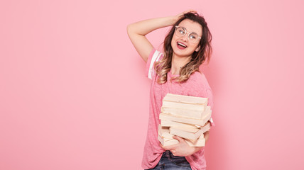 Portrait of a girl with a stack of books on a pink background