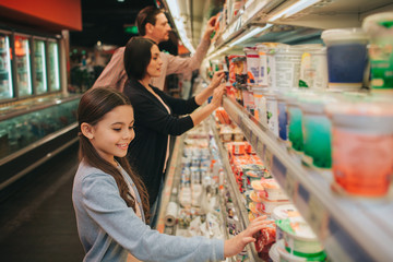 Young parents and daughter in grocery store. They stand at dairy shelf and choosing. Girl touch jars and look down. Parents stand behind.