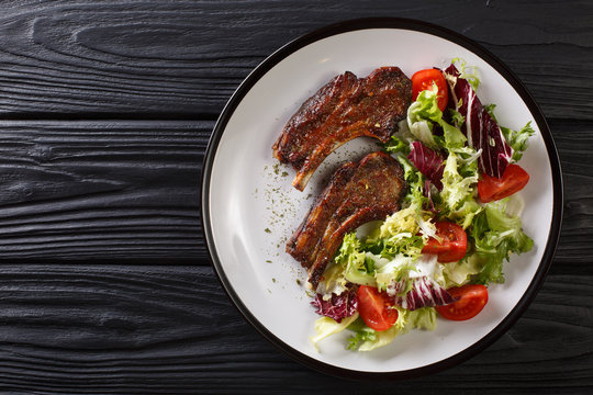 Delicious fried lamb chops served with fresh vegetable salad close-up on a plate. Horizontal top view