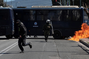 A hooded youth runs away from a riot police officer after throwing a petrol bomb as school students protest against a draft bill on education system reforms in Athens