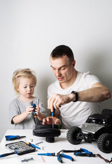 Family time: Dad and daughter repair the rc radio controlled buggy car model and lead a video blog.