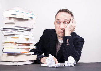 Man with books on desk struggle with writing on white background