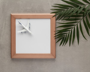 wooden picture frame airplane grey palm leaf cement palm top view with copy space for your text. flat lay.