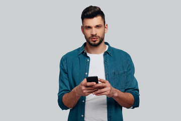 Text messaging. Charming young man using his smart phone and looking at camera while standing against grey background