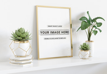 Vertical Frame Laying on Shelf With Plants Mockup