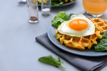 Spinach cheese waffles with fried egg on gray wooden background. Selective focus.