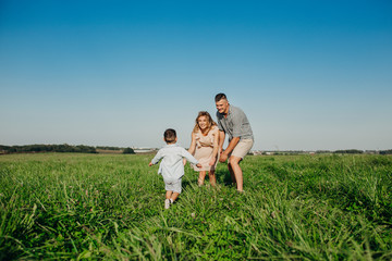 Little boy running to his mother and father in field