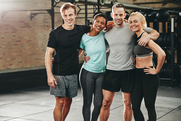 Smiling group of diverse friends standing in a gym Wall mural