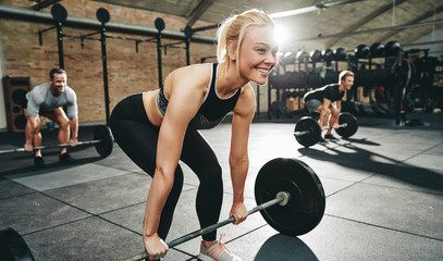 Smiling young woman in a gym weightlifting class