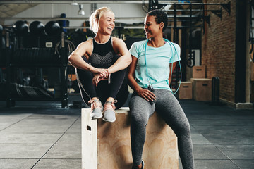 Fit young female friends laughing together after a gym workout