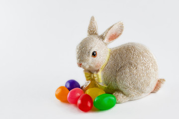 Close up of Easter bunny figurine with jelly beans isolated on white background.  Copy space.