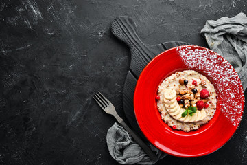 Oatmeal with nuts, banana and wild berries. In the plate. Top view. Flat lay composition Free copy space.
