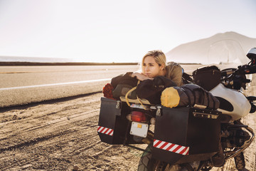 Thoughtful woman lying on motorcycle at roadside against sky