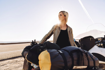Thoughtful woman standing by motorcycle at roadside against sky