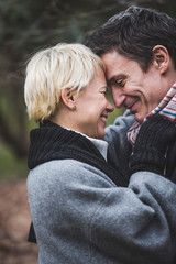 Closeup of smiling mature couple embracing outdoors