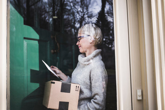 Side view of smiling woman reading envelope while receiving parcel at home