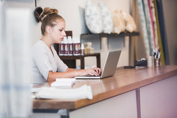 Serious owner using laptop at checkout counter in shop