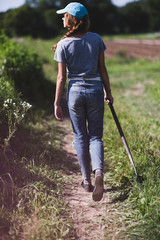Rear view of teenage farmer walking at farm