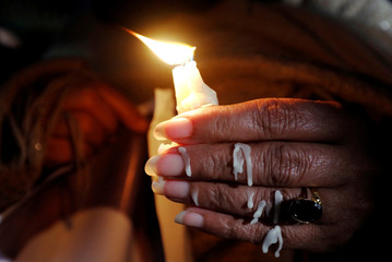 Woman with melted wax on her fingers holds a candle during a candlelight vigil for the victims of the Christchurch mosque attacks in New Zealand, in Islamabad