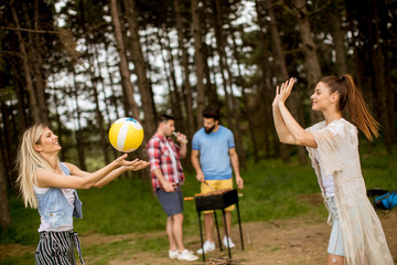 Young women playing volleyball on picnik in spring nature