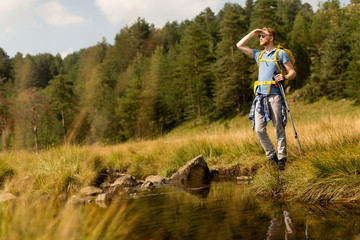 Young man crosses a mountain stream on a sunny day