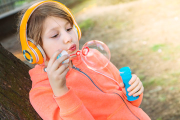 young girl listening music with headphone is blowing soap bubble