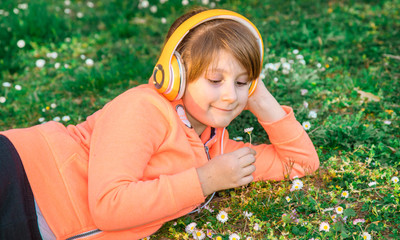 girl lying on the grass listens to music and picks up daisies