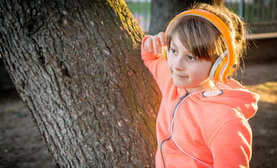 young girl is listen music with headphone to the park