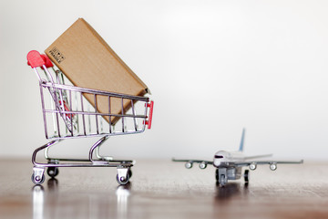 Trolley with carton and airplane. Worldwide Shopping and International shipping concept