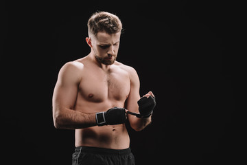 strong muscular mma fighter fixing bandages isolated on black