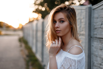 Portrait of a pretty European  young blonde woman with blue eyes with natural make-up in a stylish white lace blouse near a vintage fence at sunset. Cute girl on a walk in the summer.