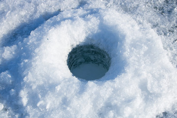Drilled hole in the ice. Winter fishing on the river.