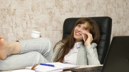 woman in office drinking coffee resting in workplace. beautiful businesswoman with phone sits in a chair with bare feet on the table resting. girl at work in office talking on a mobile phone