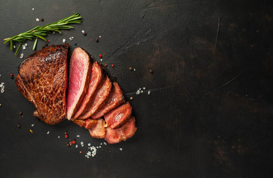 Beef steak, herbs and spices on a stone background