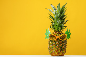 Pineapple wears sunglasses on a yellow background