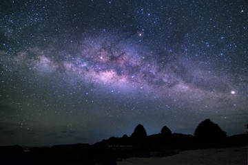 silhouette of rocks under galaxy