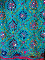 Colorful handcraft embroidery pattern on blue clothes in Indian shop in market, Thailand.