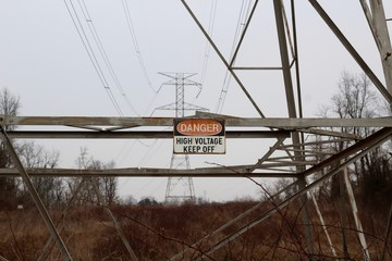 A danger sign hanging off the bottom of power tower.