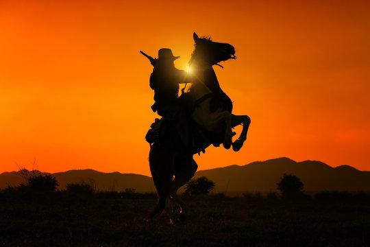 Silhouette Cowboy holding short gun and riding a horse