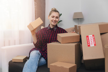 woman sit on couch at home with lot of cardboard boxes