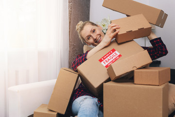 consumerism concept - happy woman with cardboard boxes at home after shopping