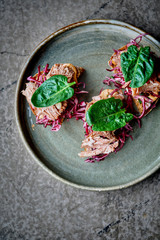Rye bread bruschetta with stewed pork, red cabbage, spicy sauce and spinach