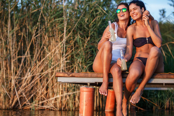 Two girls sitting and having fun on the pier by the lake on sunset.